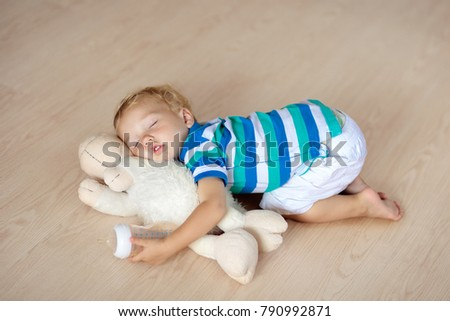 Baby sleeping on wooden floor with stuffed toy sheep and milk bottle. Funny tired little boy falling asleep crawling on hardwood floor at home. Sleepy infant drinking formula on soft cushion.