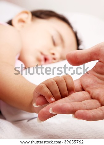 Baby sleeping take the hand of her mother - stock photo