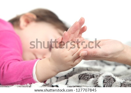 Baby sleeping takes the hand of her mother over a blanket in a white background - stock photo