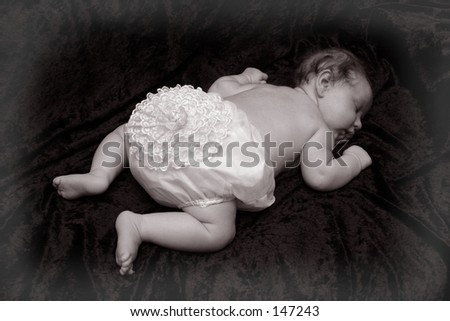 Baby sleeping with frilly pilchers.