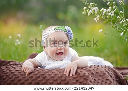 baby smiling and looking up to camera outdoors in sunlight  - stock photo