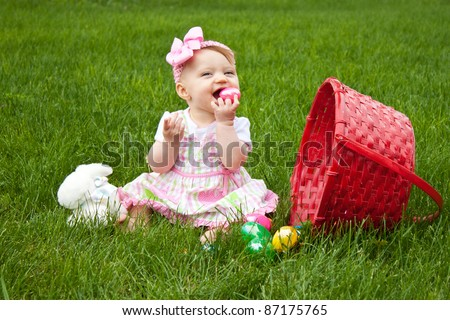 Baby Smiling while holding an Easter egg beside a red basket - stock photo