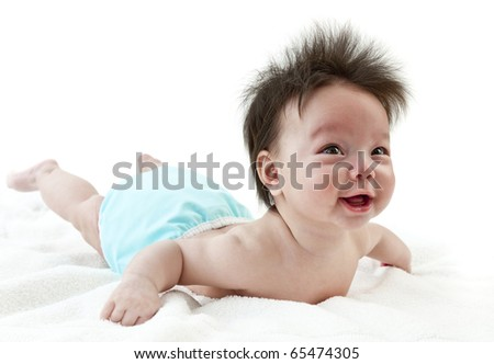 Baby smiling while practicing tummy time. Baby wearing cloth diaper - stock photo