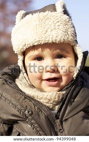 Baby smiling with hot cap - stock photo