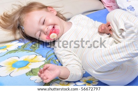 baby smiling with pacifier on the bed - stock photo