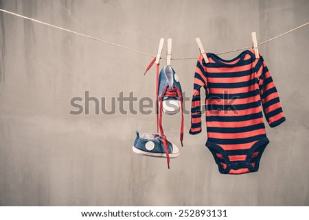 Baby sneakers and onesie   - stock photo