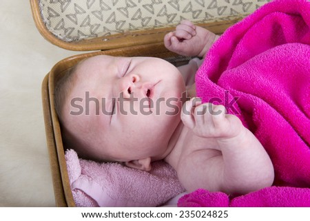 baby sneezing	. baby in a vintage suitcase sneezing  - stock photo