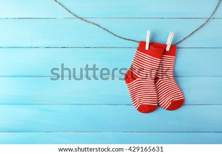 Baby socks hanging on light blue background