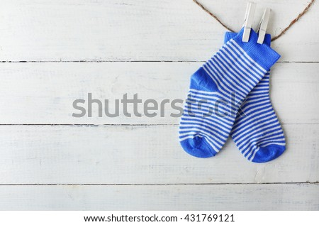 Baby socks hanging on white wooden background - stock photo