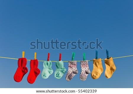 Baby socks on clothesline to dry. Blue sky. - stock photo