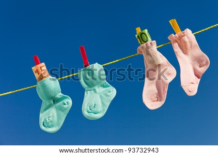 baby socks on clothesline with euro banknotes. blue sky. - stock photo