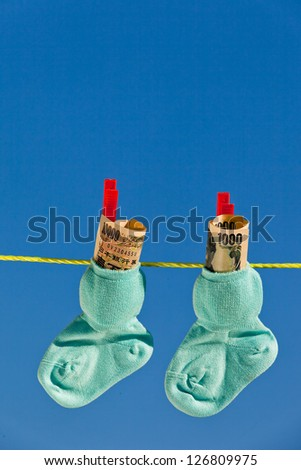 baby socks on clothesline with yen bills from japan. - stock photo