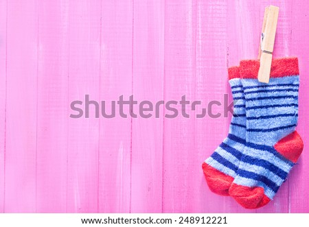 baby socks on the pink wooden table - stock photo
