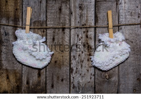 Baby socks with a clothespin on a wooden background - stock photo