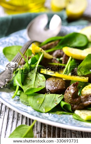 Baby spinach salad with beef liver and apple on vintage plate.