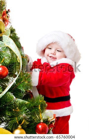 Baby standing on a step ladder and decorating Christmas tree - stock photo
