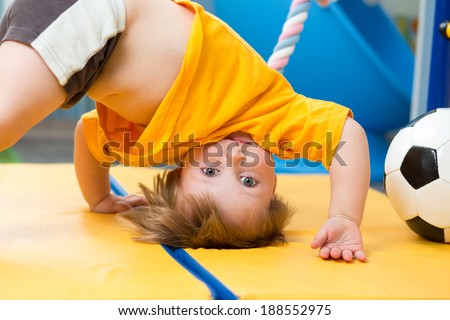 baby standing upside down on gym mat - stock photo