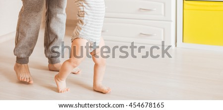 baby steps with the help of his mother - stock photo