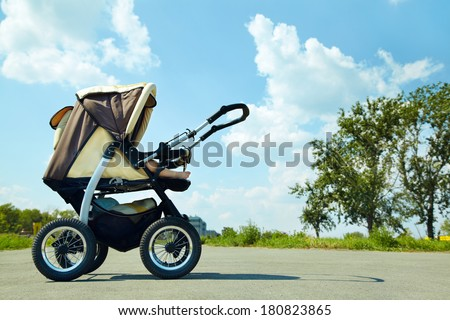 baby stroller on a walk in the park summer day - stock photo