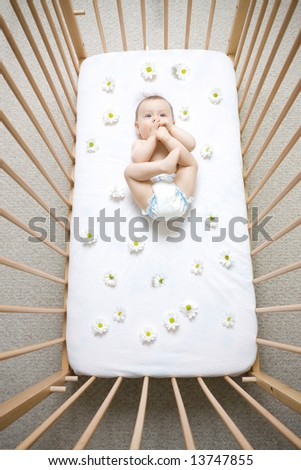 Baby sucking on feet in crib with flowered daisy sheets, caucasian/white. - stock photo