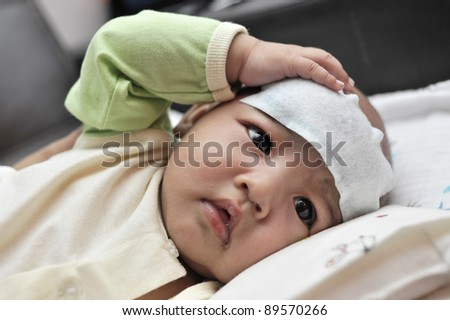 Baby suffering heat from fever - stock photo