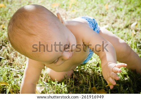 Baby sunbathing in the garden - stock photo