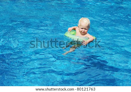 Baby swimming in the blue pool water - stock photo