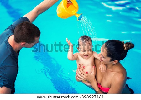 Baby swimming lessons - baby, mother and instructor having fun in the swimming pool - stock photo