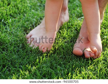 Baby taking first steps with father help in summer garden - stock photo