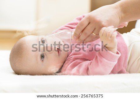 Baby taking respiratory therapy. Hand holding the mask of a nebuliser. - stock photo