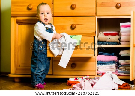 Baby throws out clothes from wooden furniture at home - stock photo