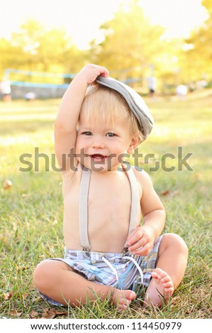 Baby, toddler boy wearing suspenders and a country / newsboy hat, outdoors, featuring seasonal, fall colors, suitable for Thanksgiving or Halloween or Fall theme - stock photo