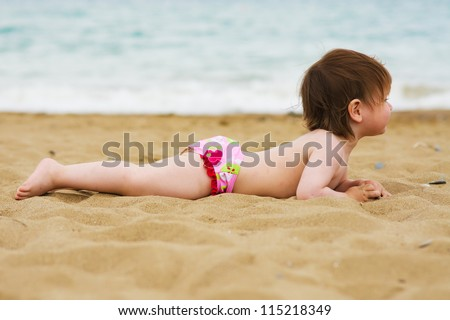 baby toddler girl laying on the sand beach takes sunbathe - stock photo