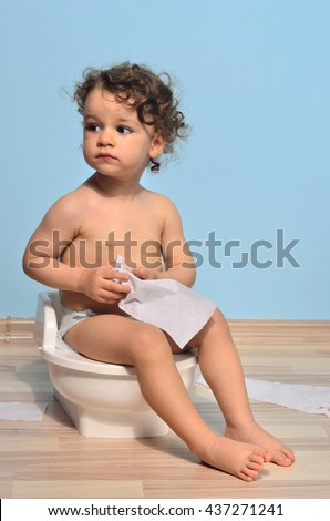 Baby toddler sitting near the potty and playing with toilet paper. Cute kid potty training for pee and poo - stock photo
