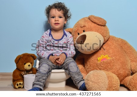 Baby toddler sitting on a potty surrounded by teddy bears. Cute kid potty training for pee and poo helped by teddy bear who gives him toilet paper - stock photo