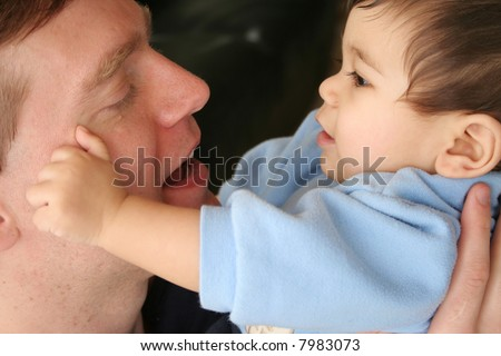 Baby touching Dad's face and talking together.