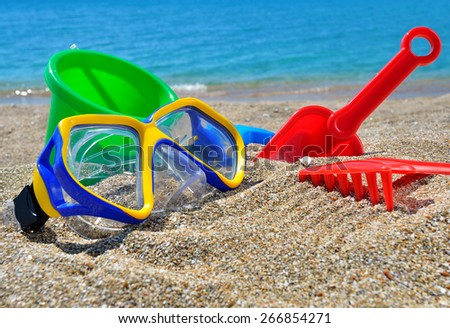 Baby Toys on the beach sand against the blue sea - stock photo