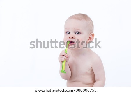 Baby trying to brush the teeth with green toothbrush - stock photo