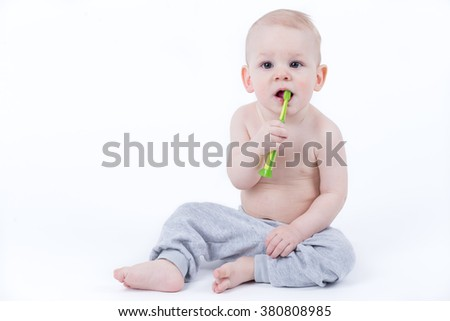 Baby trying to brush the teeth with green toothbrush