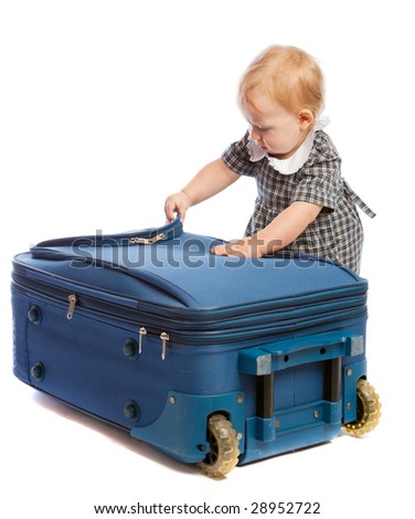 Baby trying to open a suitcase - stock photo