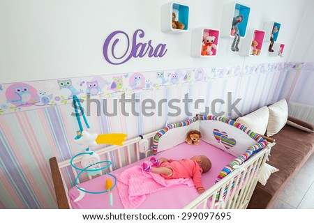 Baby twins room with pastel wallpapers and white cradles - stock photo