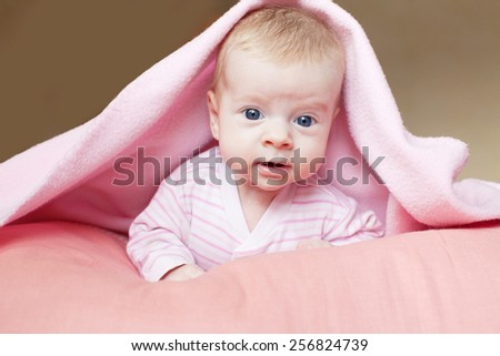 Baby under blanket. Little child at home - stock photo