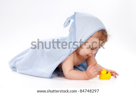 baby under blue towel playing with rubber duck on white background
