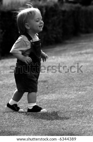 Baby Walking across the grass, black and white, high contrast - stock photo