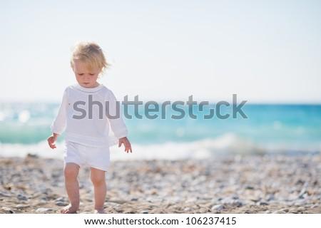 Baby walking on beach - stock photo