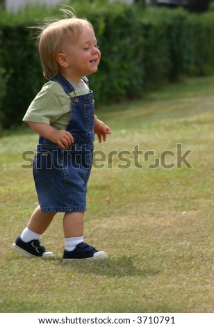 Baby walking, smiling, wind blowing his blond hair, pure joy - stock photo