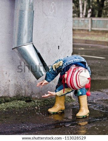 Baby washes up on the street under the drain. - stock photo