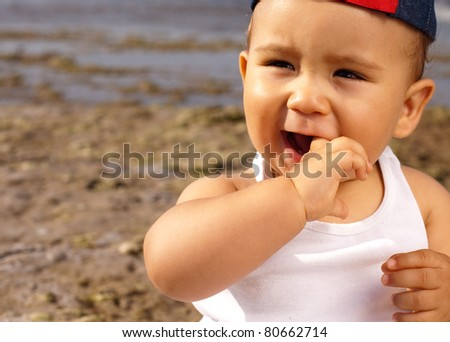 baby wearing a cap in the beach