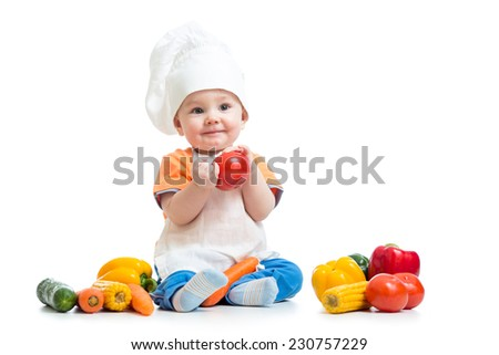 Baby wearing a chef hat with fesh vegetables - stock photo