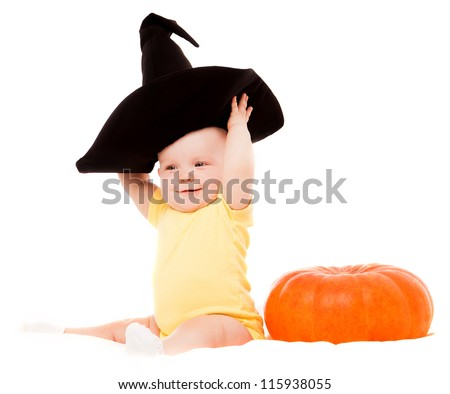 baby wearing a witch's hat with a big  pumpkin - stock photo